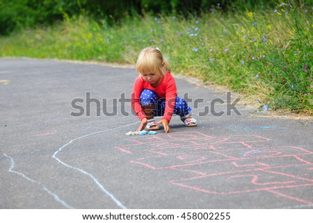 little girl drawing hopscotch on playground - stock photo