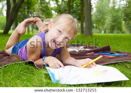 little girl drawing in the park on the grass - stock photo