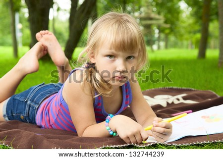 little girl drawing in the park on the grass