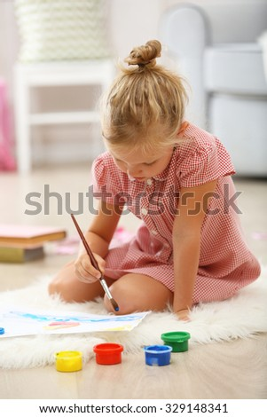 Little girl drawing in the room