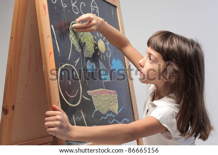 Little girl drawing on a blackboard - stock photo