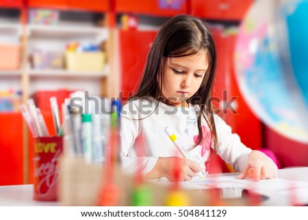 Little girl drawing on her book and having fun at playtable