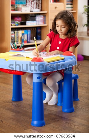 little girl drawing on her book at playtable - stock photo