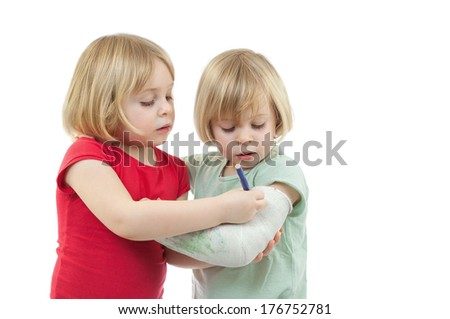 Little girl drawing on her twin sister's plaster cast. - stock photo