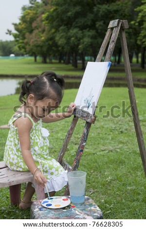 Little girl drawing /painting pictures in the park. - stock photo