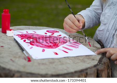little girl drawing red heart. Mothers Day. Fathers day. Valentines day. Birthday  - stock photo