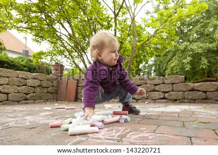 little girl drawing with chalk on ground of the terrace. - stock photo