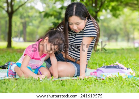 Little girl drawing with her mother laying on the grass