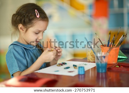 Little girl drawing with paints at home - stock photo
