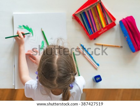 Little girl drawing with pencil at home. Top view. - stock photo