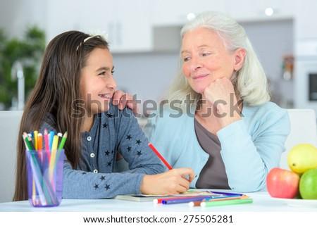 Little girl drawing wuth grandma - stock photo