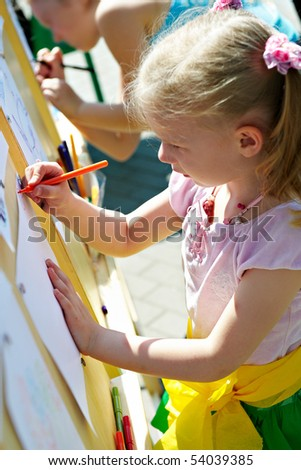 Little girl draws on a sheet of paper on a big stand in the house of creativity