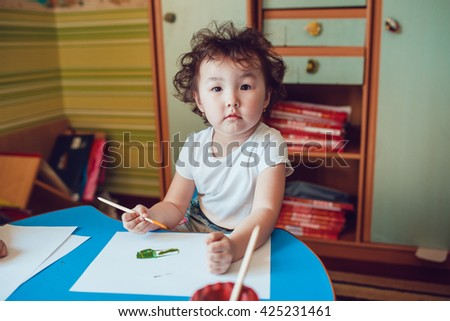 Little girl draws on watercolor paper