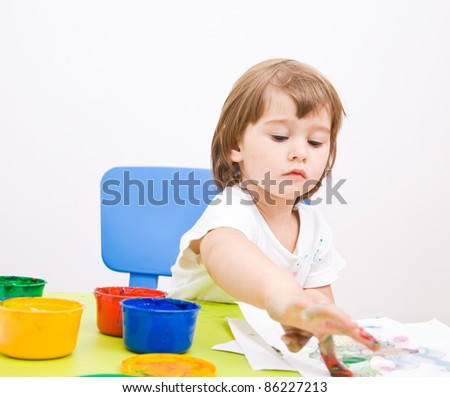 little girl draws paint sitting at the table