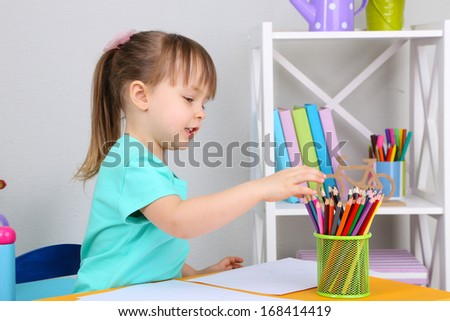 Little girl draws sitting at table in room