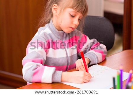 Little girl draws sitting at table in room.