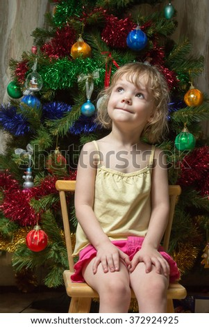 little girl dreamily looking up on a chair near the Christmas tree