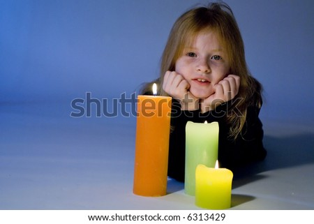 Little girl dreaming by candles - stock photo
