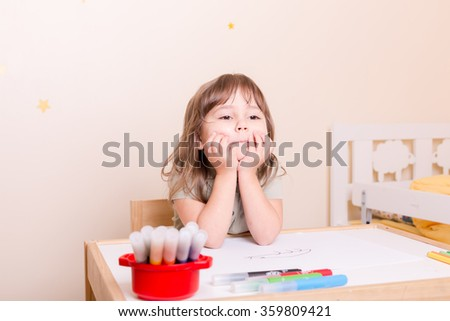 little girl dreaming sitting at the table in preschool - stock photo