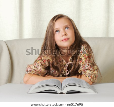 Little girl dreams about something when reading the book.