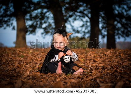 Little girl dreassed as a which sitting in a park on fallen leaves. Wearing black robe and hat with a spider. Holding a skull pot
