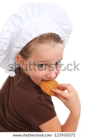 Little girl dressed as a chef eating a cookie - stock photo