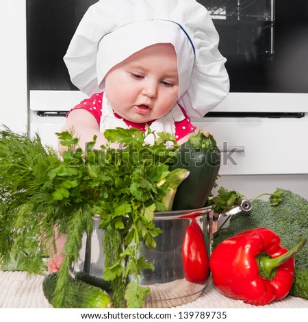 little girl dressed as a chef preparing a meal at home in the kitchen - stock photo