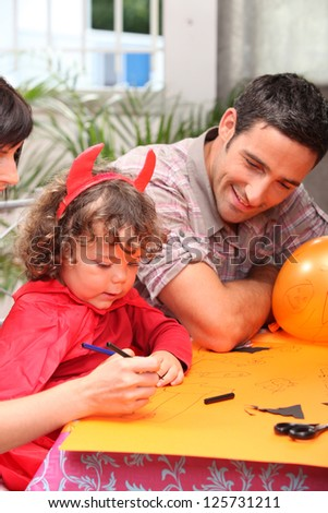 little girl dressed as a devil drawing - stock photo
