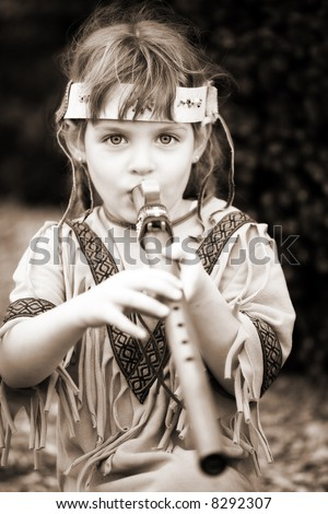 Little girl dressed as a Native American playing a wooden flute.  In sepia tone.