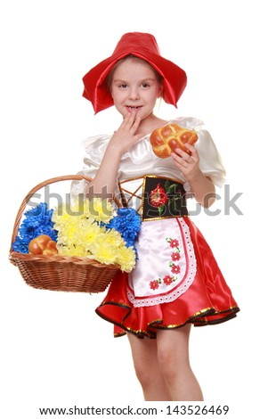 Little girl dressed as Little Red Riding Hood is holding a basket of cakes and flowers on a white background