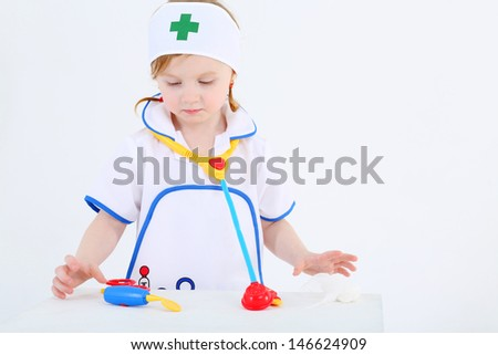 Little girl dressed as nurse plays with toy medical instruments on white background. - stock photo