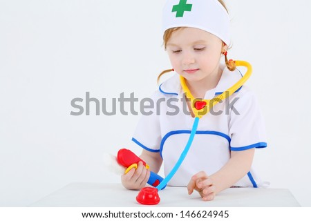 Little girl dressed as nurse plays with toy phonendoscope and medical instruments on white background. - stock photo