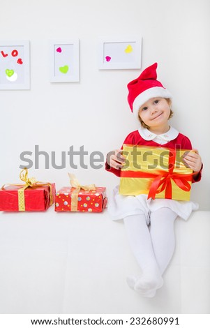 little girl dressed as Santa sitting on the couch with a Christmas present - stock photo