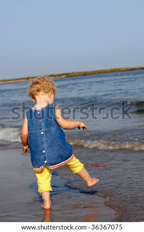 Little girl dressed at the seashore ready to try the water with one foot