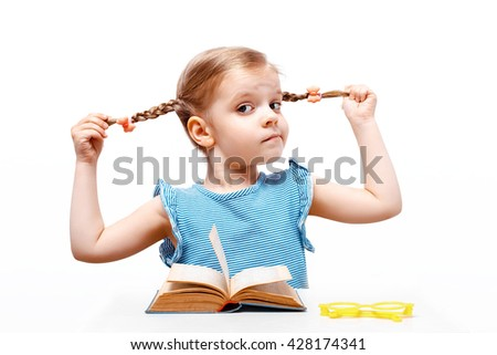 Little girl dressed in a blue shirt with strips, holds with hands her hair braids so far sits at a table. on a table lies a book and yellow glasses. white background. isolate. - stock photo