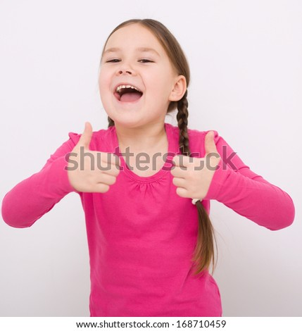 Little girl dressed in blue is showing thumb up gesture using both hands - stock photo