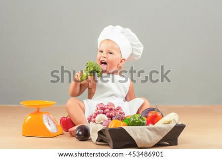 Little girl dressed in white chef hat and apron, eats only vegetables. The child weighed on the scales Products: eggplant, onion, garlic, pumpkin, red and green peppers, cabbage, tomatoes