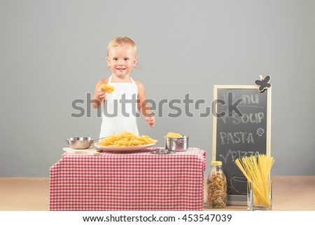 Little girl dressed in white chef hat and apron preparing pasta. Child blonde in the kitchen helps parents to prepare lunch - stock photo