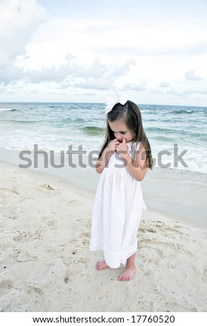 Little girl dressed in white pouting while standing on the beach with the ocean in the background. - stock photo