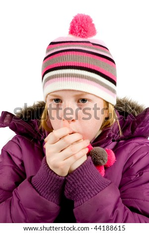 little girl dressed in winterclothes blowing her hands warm on white
