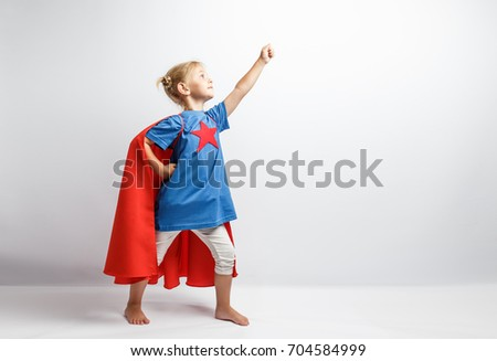 Little girl dressed like superhero standing alongside the white wall.