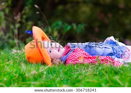 Little girl dressed up as cowgirl playing with toy rocking horse in park. Kids play cowboy outdoors. Children in Halloween costumes at trick or treat. Toys for preschooler kid or toddler child. - stock photo