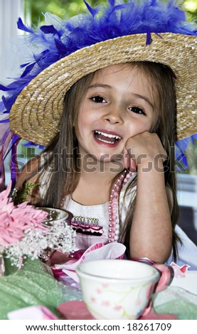Little girl dressed up for a tea party with a fancy hat and pink beads. - stock photo
