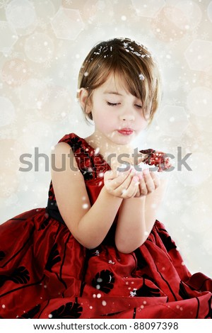 Little girl dressed up for the holidays blows snow from her hands. - stock photo