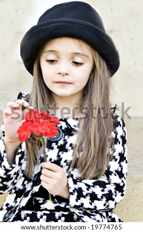 Little girl dressed with a coat and hat holding a red flower - stock photo