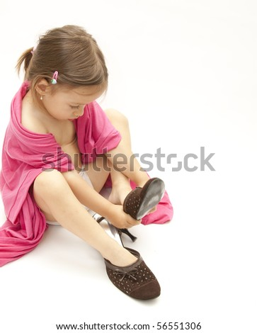 little girl dressing with her mother shoes and cloths - stock photo