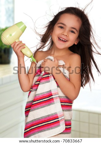 Little girl dries hair after bathing in bathroom - stock photo