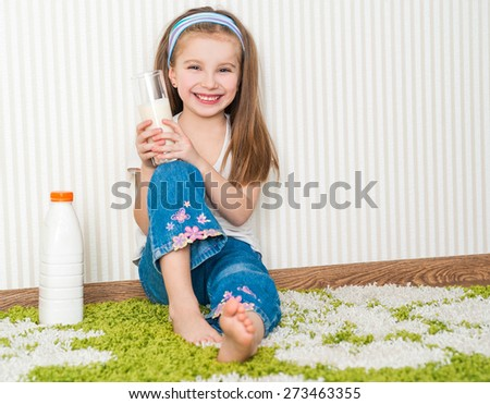 little girl drink the milk  on the floor in her home - stock photo