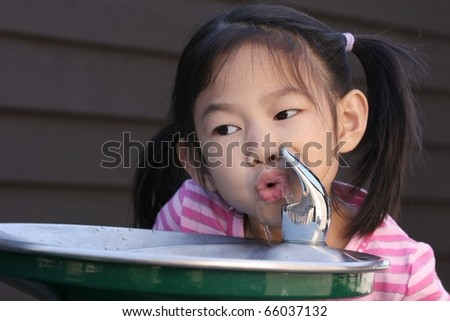 little girl drink water from water fountain - stock photo