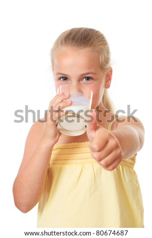 little girl drinking a glass of milk and holding her thumb up - stock photo